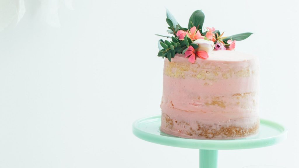 Semi-naked wedding cake with a pink buttercream crumb coating